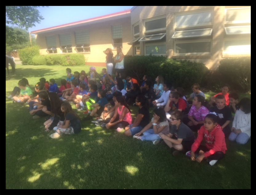 Kemper School 3rd grade class gather together to see the winner of the contest at their school.